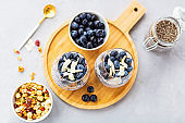 Chia pudding with granola and fresh blueberries in the glasses on a gray concrete background with copy space. Concept of healthy eating, healthy lifestyle, dieting, fitness menu. Selective focus