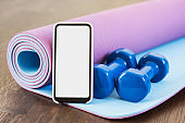 Fitness at home, smartphone app for online training, dumbbells and mat