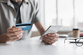 Man paiyng online with smartphone and credit card