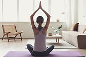 Young woman practicing yoga, meditating at home