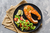 Fried salmon fish steak with vegetable salad and lemon on black plate. Creative layout made of fish, lettuce, tomato, cucumber, top view, flat lay, mockup, overhead. Healthy food concept