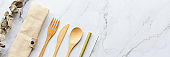 Set of Eco friendly bamboo cutlery on white marble background. Sustainable lifestyle. Plastic free concept. Flat lay, top view, mockup