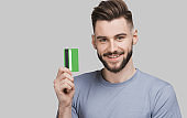 Handsome young man showing credit card