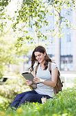 Beautiful student girl using digital tablet in a city