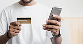 Online shopping concept. Man using smartphone and paying with credit card