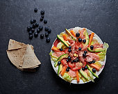 Salmon salad with avocado, fresh vegetables, blueberries, ginger, goji berries and seeds