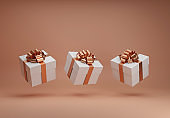 White gift boxes with golden ribbon bow levitating on natural beige background. Flying present abstract commercial concept. Creative minimal banner with copy space. 3d render