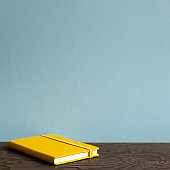 Yellow diary note book on wooden desk. sky blue background