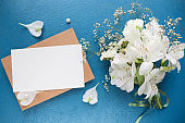 postcard mockup. bouquet of white flowers on a blue background