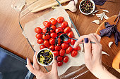 Cropped view of woman adding cut basil leaves with olive oil to tomatoes in baking dish on wooden background