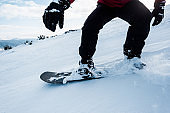 cropped view of snowboarder in gloves riding on slope with white snow in wintertime