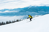 sportsman holding sticks and skiing on slope with snow in mountains