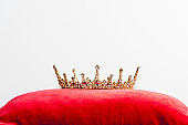 royal crown on red pillow isolated on white with copy space