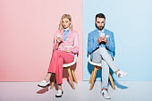 attractive woman and handsome man using smartphones on pink and blue background