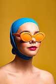 attractive naked woman in scarf and fashionable sunglasses, isolated on yellow