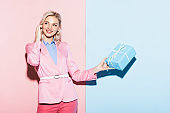 smiling woman holding gift box on pink and blue background