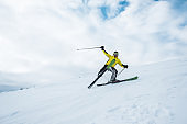 excited sportsman holding ski sticks and skiing on white slope