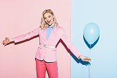 smiling woman holding balloon on pink and blue background