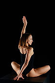 girl in lotus pose with outstretched hand practicing yoga isolated on black