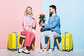 handsome man giving bouquet to shocked woman on pink and blue background