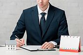 cropped view of realtor writing near blank calendar and house model on white, leasing concept