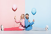 back to back view of smiling woman and handsome man with balloons showing yes gesture on pink and blue background