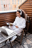 happy african american freelancer in wireless headphones reading magazine near laptop and cup