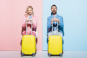 smiling woman and handsome man holding travel bags on pink and blue background