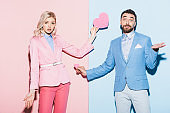 shocked woman and handsome man holding heart-shaped cards on pink and blue background