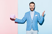 handsome and smiling man holding gift on blue and pink background