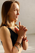 beautiful young woman with clenched hands in yoga studio