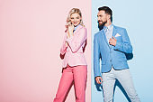 attractive woman and smiling man looking at her on pink and blue background