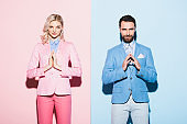 attractive woman and smiling man with praying hands on pink and blue background