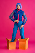 fashionable girl in purple wig standing in cardboard boxes on pink