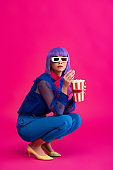 attractive pop art girl in purple wig and 3d glasses eating popcorn, on pink