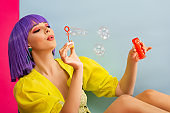 happy attractive girl in purple wig as doll blowing soap bubbles while sitting in blue box, isolated on pink