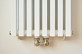 white and modern heating radiator near wall in apartment