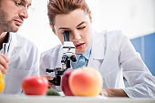 selective focus of molecular nutritionist using microscope and colleague holding test tube