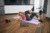 Woman training abs at home using video on laptop.