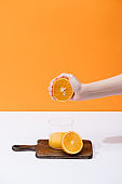 cropped view of woman squeezing fresh orange juice in glass on wooden cutting board on white surface isolated on orange