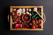 top view of tomato sauce with basil leaves near cherry tomatoes, green chili peppers, mushrooms and rosemary in wooden box on black
