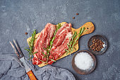 Raw blade steak of marbled beef on wooden board over dark background. Top view from above