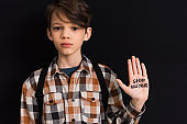 sad schoolboy with stop bullying lettering on hand isolated on black