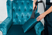 cropped view of cleaner dry cleaning pillow on modern armchair with vacuum cleaner
