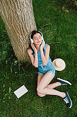 high angle view of beautiful woman in closed eyes listening music while sitting on grass near book and straw hat