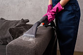 Cropped view of cleaner using vacuum cleaner with hot steam on couch upholstery