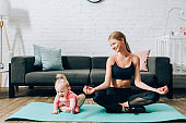 Woman looking at baby daughter while meditating on fitness mat at home