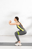 side view of athletic girl doing squat while exercising with resistance band on fitness mat