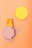 Top view of paper cut sun, beach umbrella and blanket with dispenser bottle of sunscreen on orange