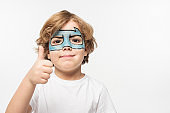 cheerful boy with superhero mask painted on face showing thumb up while looking at camera isolated on white